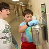 Allegra Boverman/Gloucester Daily Times. Essex Elementary School fifth graders Jes MacDonald, left, and Tim Reilly are part of the Green Team and it's their job to check on, empty and put new bags into the wall-mounted composting buckets that are positioned in all the hallways at the school.