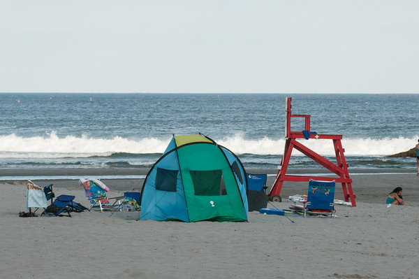 DESI SMITH/Staff photo.   Beach goer's set up camp at Good Harbor Beach Thursday afternoon as the Labor Day weekend approaches, ending summer. August 28,2014