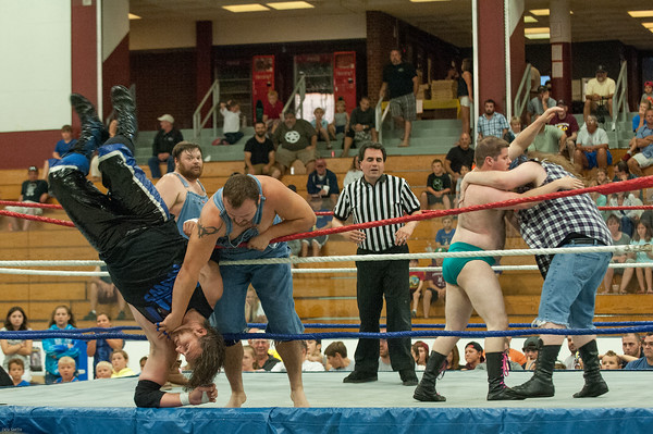"DESI SMITH/Staff photo.  ""The Country Boys"" (in jeans) Lumber Jake,Cousin Larry and Hunter Ward, take care of business in a tag team match against Big Bear Matouch ,Beau Douglass and Kyle Huntly, Friday night at the O'maley Rink for the Police Relief Assoiation Wrestling.  August 16,2014"
