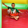 AMY SWEENEY/Staff photo. Ryder Huseby, 8, flies down a slide at the Sidewalk Bazaar.