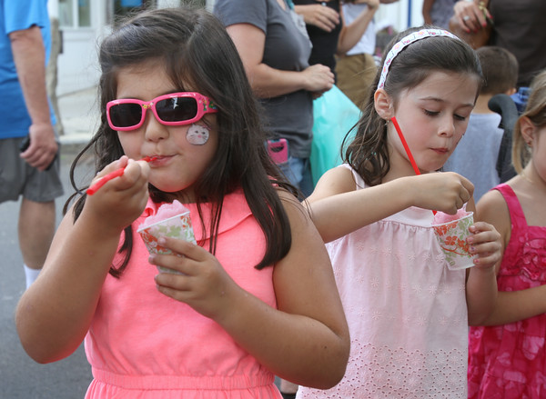 AMY SWEENEY/Staff photo. Emma Carrapichosa, 6, and Talia Harrington, 6,  eat a slush during the SIdewalk Bazaar on Thurday morning.  8.7.14