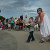 "DESI SMITH/Staff photo.   Carol Gray of Gloucester,walks with her grandson Wallace Gray III 4, as he goes to place a wreath in memory of his father Wallace ""Chubby"" Gray II who was lost on the Foxy Lady II in 2012, during a Gloucester Fishermen's Memorial Service held Saturday at the Man at the Wheel statue on Stacy Blvd.    August 16,2014"