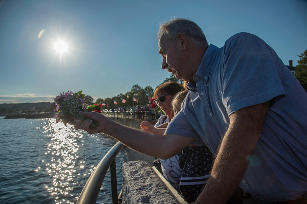 Desi Smith Photo.  Bill McDonald along with his granddaughter Adeline Hebert 21 months and his wife Annette Parisi McDonald of Gloucester, toss flowers remembering her father  during the Annual Gloucester Fishermen's Memorial Service held Saturday afternoon on Stacey Boulevard.  August 27,2016.