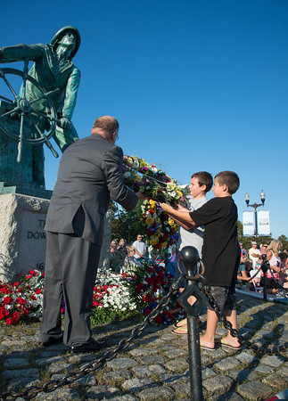 Desi Smith/Staff Photo.   Sal Russo 10, and brother John 7, gets some help from Joe Parisi placing a wreath at the base of the fishermens statue remembering their father Capt. John Matteo Russo and grandfather John Orlando who went down at sea aboard the F/V Patriot in January 2009, during the Annual Gloucester Fishermen's Memorial Service that was held Saturday afternoon on Stacey Boulevard.  August 27,2016.
