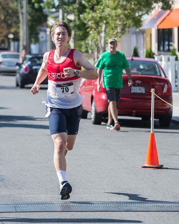 Desi Smith Photo.    Ipswich's Dan O'Flynn crosses the finish placing first for the men at 17:24 as his father looks on, in the Magnolia 5k Road Race held Saturday morning in Magnolia.  August 27,2016