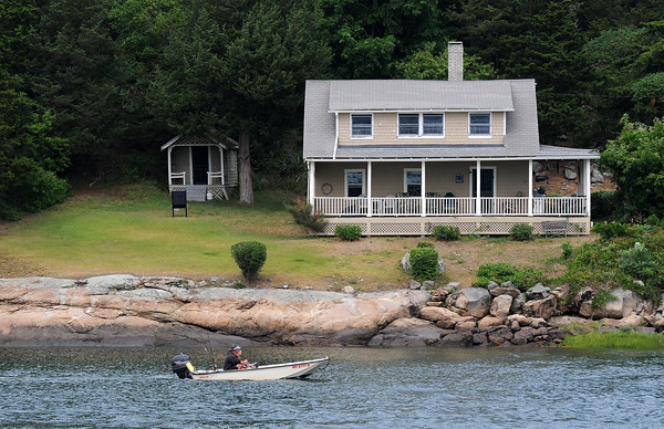 PAUL BILODEAU/Staff photo. An angler passes by a home on Cross Island in Essex while heading out toward Ipswich Bay near Conomo Point.