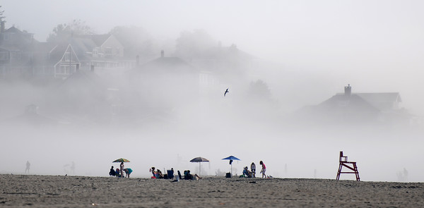 PAUL BILODEAU/Staff photo.Beach goers staking out their spots in the morning at Good Harbor Beach as the fog slowly lifts from the beach.  8/11/16