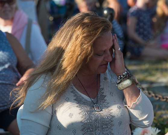 """Desi Smith Photo.  A woman greaves the loss of Gloucester Fishermen Capt.David """"Heavy D"""" Sutherland who went down aboard the Orin C on December 3rd 2015 during the Annual Gloucester Fishermen's Memorial Service held Saturday afternoon on Stacey Boulevard.     August 27,2016."""
