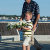 "Desi Smith Photo.  Wallace Gray III 6, walks with his grandfather Wallace Gray of Gloucester to place a wreath at the Fishermens Monument remembering his father Wallce ""Chubby"" Gray Jr who lost his life aboard the Foxy Lady II 2012, at the Annual Gloucester Fishermen's Memorial Service held Saturday afternoon on Stacey Boulevard.     August 27,2016."