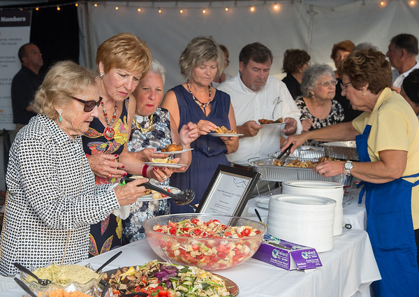 Desi Smith Photo.       Server Rosalee Nicastro (far right) serves guest as they make their way down the line of seafood creations by Chef Todd Snopkowski of Snap Chef during the Sea to Supper Celebration and fundraiser Thursday night at Mile Marker One Restaurant & Bar at Cape Ann's Marina Resort. August 24,2017