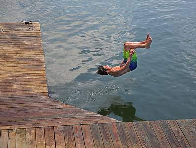 MIKE SPRINGER/Staff photo Nicholas White, 13, jumps from the dock at Lobster Cove in Annisquam.