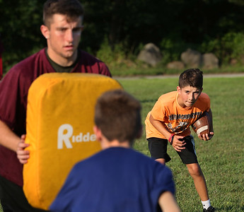 MIKE SPRINGER/Staff photo Fifth-grader Jackson Cody carries the ball in a defensive drill led by varsity captain Ryan Argentino, left, during a special Youth Fishermen football practice with GHS varsity coaches and captains Thursday at the Green Street field in Gloucester. In the foreground is fifth-grader Tyler Chepulis. 8/16/2018
