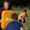 MIKE SPRINGER/Staff photo<br /> Fifth-grader Jackson Cody carries the ball in a defensive drill led by varsity captain Ryan Argentino, left, during a special Youth Fishermen football practice with GHS varsity coaches and captains Thursday at the Green Street field in Gloucester. In the foreground is fifth-grader Tyler Chepulis.<br /> 8/16/2018
