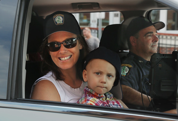 MIKE SPRINGER/Staff photo Two-year-old Will Bren rides with his mother, Cara, in a police car driven by detective Thomas Quinn Tuesday on Main Street in downtown Gloucester. 8/14/2018