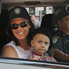 MIKE SPRINGER/Staff photo<br /> Two-year-old Will Bren rides with his mother, Cara, in a police car driven by detective Thomas Quinn Tuesday on Main Street in downtown Gloucester.<br /> 8/14/2018