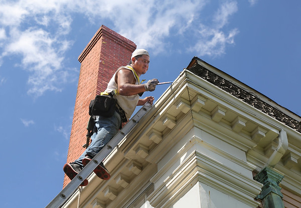 MIKE SPRINGER/Staff photo<br /> A worker with the Melrose-based Olde Mohawk historic preservation company works Thursday on the roof of the Sargent House Museum in Gloucester. Cedar shingles had been falling off the roof of the historic house for the past three or four years, so the museum applied for a Community Preservation Act grant in 2017 and was awarded $61,500 for renovations. The winning bidder, Olde Mohaw, is replacing the cedar shingles visible from the street and the asphalt shingles at the top of the building, repairing cedar gutters and lining them with copper, and replacing rotted trim wood around the dormer windows.<br /> 8/2/2018