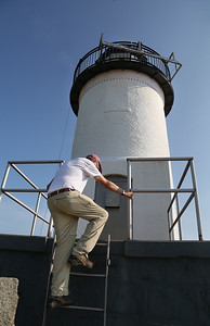 MIKE SPRINGER/Staff photo Volunteer worker Ed Hand climbs up to the lighthouse on Straitsmouth Island in Rockport. 8/8/2018