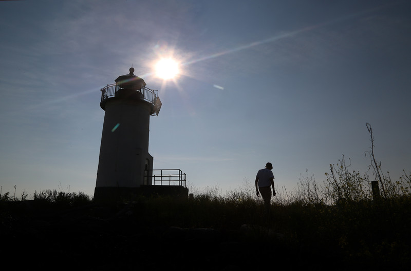 MIKE SPRINGER/Staff photo Volunteer worker Ed Hand walks near the lighthouse on Straitsmouth Island in Rockport. 8/8/2018
