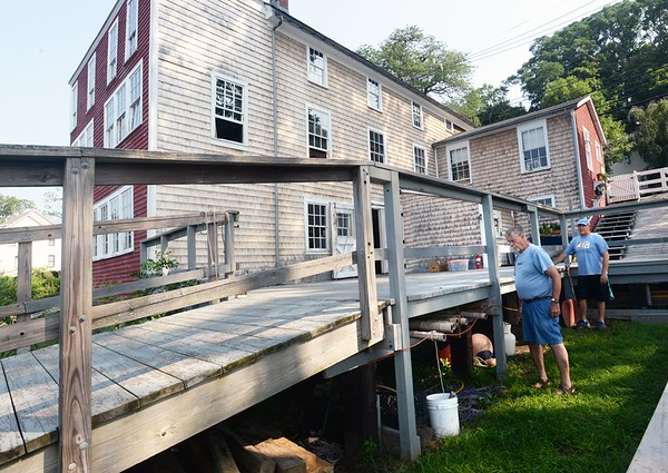 BRYAN EATON/Staff photo. Ken Turner, left, and Frank Goldberg lay lines as they put up decorative lighting at Lowell's Boat Shop for their pig roast fundraiser next weekend. [[MER1808161735334074]]