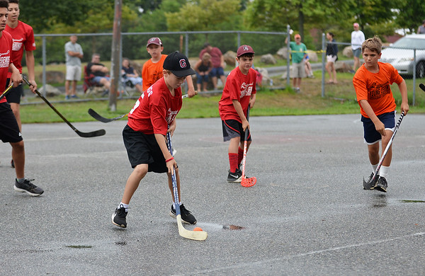 RYAN HUTTON/ Staff photo<br /> The Red Wings' Sean Broe readies a hard pass during the Young Legends Youth Street Hockey League's finals at the Stage Fort Park basketball courts on Sunday.