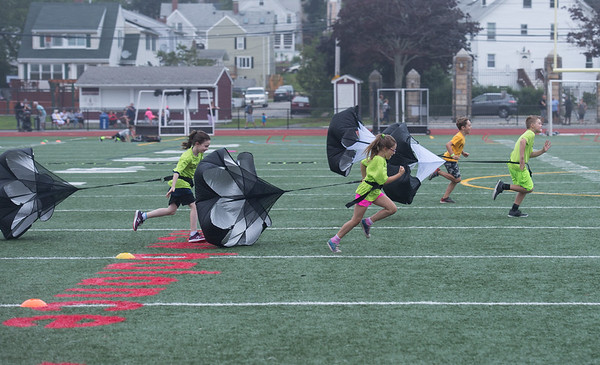 Desi Smith Photo.   Boys and girls sprint across the field with a parachute strapped to their waist for some drag, during the Youth Track and Field, held late Wednesday afternoon at the New Balance Track and Field at Newell Stadium.     August 1,2018