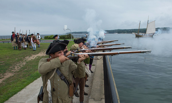 Desi Smith Photo.   A militia group wearing period clothing, fire upon the enemy during a reenactment of the 1775 Battle of Gloucester on the Outer Harbor, off Pavilon Beach Saturday morning.  August 11,2018.