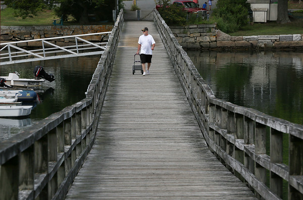 MIKE SPRINGER/Staff photo<br /> Boater Michael Lindberg of Gloucester walks down the wooden footbridge over Lobster Cove at Annisquam. Decades ago, there was a car bridge where the foot bridge is today.<br /> 8/9/2018