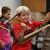 "MIKE SPRINGER/Staff photo<br /> Seven-year-old Jacoby Numerosi participates in a ""jug band"" sketch during a performance Friday by ""Spoon Man"" Jim Cruise of Jenison, Michigan at the Sawyer Free Library. The performance was part of a wrap-up party for the library's summer reading program for children.<br /> 8/10/2018"