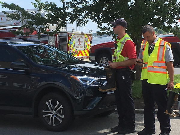 ANDREA HOLBROOK/Staff Writer/Gloucester fire Lt. Kevin Gaygan, left, collects muscular dystrophy donations Friday on Western Avenue as Lt. Jamie Santos takes a call about a ring found in firefighter Lukas McRobb's boot earlier.