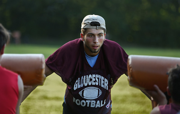MIKE SPRINGER/Staff photo Varsity football captain Marc Smith leads a drill on the sled during a special Youth Fishermen football practice with GHS varsity coaches and captains Thursday at the Green Street field in Gloucester.  8/16/2018