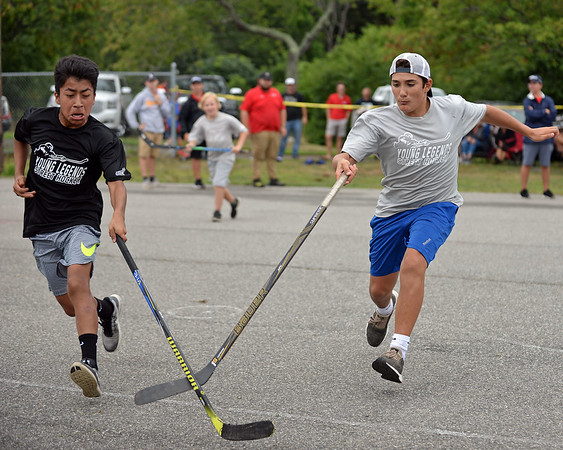 RYAN HUTTON/ Staff photo<br /> The Blackhawks' Gus Nugent, left, and the Rangers' Jack Contanzo, right, race toward the ball during the Young Legends Youth Street Hockey League's finals at the Stage Fort Park basketball courts on Sunday.