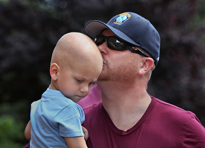 MIKE SPRINGER/Staff photo Craig Bren kisses his son Will, 2, during an event in support of Will on Tuesday at Gloucester police headquarters. Will is battling cancer. 8/14/2018