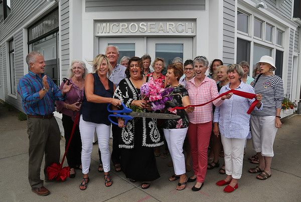 MIKE SPRINGER/Staff photo Susan Kelly holds the scissors as Mayor Sefatia Theken, center, and other guests help her cut the ribbon Wednesday at the new Microsearch office on Western Avenue in Gloucester. 8/2/2018