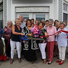 MIKE SPRINGER/Staff photo<br /> Susan Kelly holds the scissors as Mayor Sefatia Theken, center, and other guests help her cut the ribbon Wednesday at the new Microsearch office on Western Avenue in Gloucester.<br /> 8/2/2018
