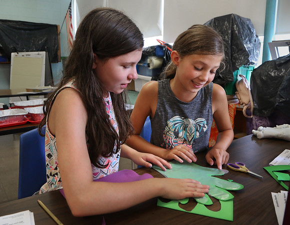 "MIKE SPRIGER/Staff photo<br /> Sixth-grader Megan Pierce, left, and Fourth-grader Jocelyn Maddalena work together to cut out a ""space glove"" using felt during a STEAM (Science, Technology, Engineering, Art and Mathematics) Camp project Thursday at Beeman Elementary School in Gloucester. The project, part of the Museum of Science's ""Engineering Adventures"" program was designed to teach the students how to solve engineering problems to select the right materials to make a glove that could withstand thermal fluctuations and impacts. The six-week STEAM Camp was offered to students going into the fourth through sixth grades, and is taught by Annemarie Wentzell and Erin Schondelmeier.<br /> 8/9/2018"