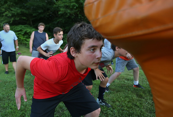 MIKE SPRINGER/Staff photo<br /> Seventh-grader Sal Russo prepares to hit the sled during a special Youth Fishermen football practice with GHS varsity coaches and captains Thursday at the Green Street field in Gloucester. <br /> 8/16/2018