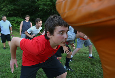 MIKE SPRINGER/Staff photo Seventh-grader Sal Russo prepares to hit the sled during a special Youth Fishermen football practice with GHS varsity coaches and captains Thursday at the Green Street field in Gloucester.  8/16/2018