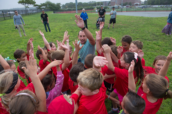 Desi Smith Photo.     Volunteer Paul Simon gets things started with a group of excited 5-6 year olds, during the Youth Track and Field held late Wednesday afternoon at the New Balance Track and Field at Newell Stadium.     August 1,2018