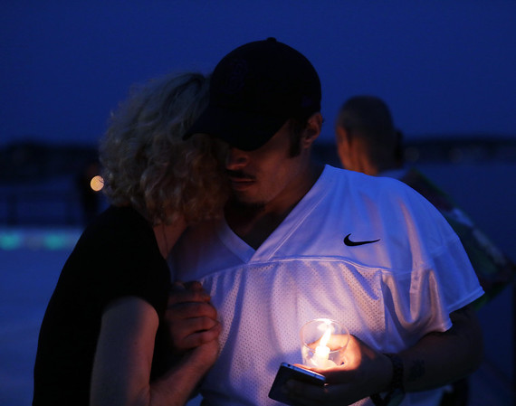 DAVID LE/Gloucester Times. Steve Woodhouse, of Gloucester, gets a hug and handshake from Angie Burnham, also of Gloucester, at a vigil held on the Boulevard to remember those lost to the Opioid epidemic.