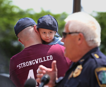 MIKE SPRINGER/Staff photo Two-year-old Will Bren looks over his father Craig's shoulder to watch Gloucester Interim Police Chief John McCarthy speak during a ceremony Tuesday in support of Will, who has cancer, in front of Gloucester police headquarters. 8/14/2018