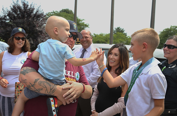 """MIKE SPRINGER/Staff photo Two-year-old Will Bren gives a """"high five"""" to 7-year-old Mason Adams during a Cops for Kids with Cancer ceremony Tuesday at Gloucester police headquarters. The family of Will, who is fighting cancer, received support from the organization, which Mason earlier raised $900 for. From left are Mason's mother Cara, Mason, his father Craig, Gloucester Chief Administrative Offier Jim Destino, Mason's mother Gretchen, Mason, and Gloucester police officer Heidi Fialho. 8/14/2018"""