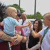 """MIKE SPRINGER/Staff photo<br /> Two-year-old Will Bren gives a """"high five"""" to 7-year-old Mason Adams during a Cops for Kids with Cancer ceremony Tuesday at Gloucester police headquarters. The family of Will, who is fighting cancer, received support from the organization, which Mason earlier raised $900 for. From left are Mason's mother Cara, Mason, his father Craig, Gloucester Chief Administrative Offier Jim Destino, Mason's mother Gretchen, Mason, and Gloucester police officer Heidi Fialho.<br /> 8/14/2018"""