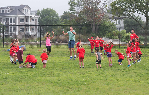 "Desi Smith Photo.     Volunteer Paul Simon (center) leads a group of excited 5-6 year olds,in a game of ""Simon Says"" during the Youth Track and Field held late Wednesday afternoon at the New Balance Track and Field at Newell Stadium.     August 1,2018"