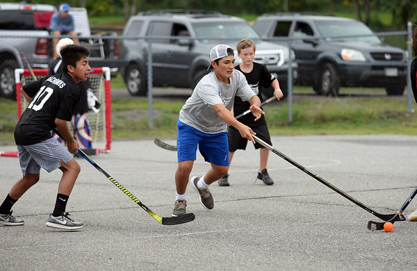 RYAN HUTTON/ Staff photo<br /> The Rangers' Jack Costanzo, right, dashes to grab the ball during the Young Legends Youth Street Hockey League's finals at the Stage Fort Park basketball courts on Sunday.