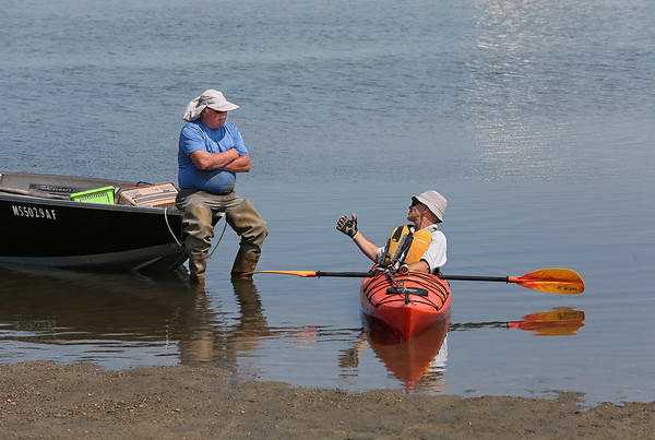 MIKE SPRINGER/Staff photo<br /> Buddy Jacobs, left, of Gloucester has a conversation with kayaker Alexander Zhelkovsky of Peabody while he waited to unload a day's catch of clams Monday at Conomo Point boat landing in Essex.
