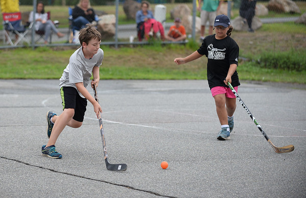 RYAN HUTTON/ Staff photo<br /> The Rangers' Wesley Prevost, left, dribbles the ball down court during the Young Legends Youth Street Hockey League's finals at the Stage Fort Park basketball courts on Sunday.