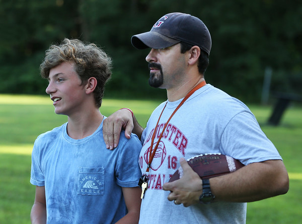 MIKE SPRINGER/Staff photo<br /> Varsity head coach Tony Zerilli instructs eighth-grader Caleb DeCoste in leading a warm up drill during a special Youth Fishermen football practice with GHS varsity coaches and captains Thursday at the Green Street field in Gloucester. <br /> 8/16/2018