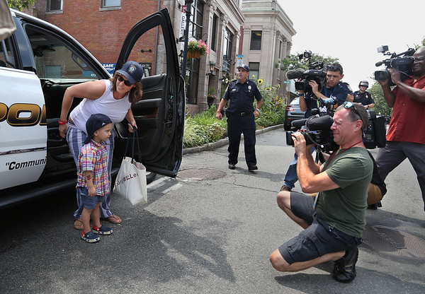 MIKE SPRINGER/Staff photo Two-year-old Will Bren steps out of a police vehicle with his mother, Cara, as television cameramen surround him Tuesday in front of Gloucester police headquarters. Will, who has cancer, was treated to a ride in a police motorcade. 8/14/2018