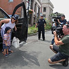 MIKE SPRINGER/Staff photo<br /> Two-year-old Will Bren steps out of a police vehicle with his mother, Cara, as television cameramen surround him Tuesday in front of Gloucester police headquarters. Will, who has cancer, was treated to a ride in a police motorcade.<br /> 8/14/2018