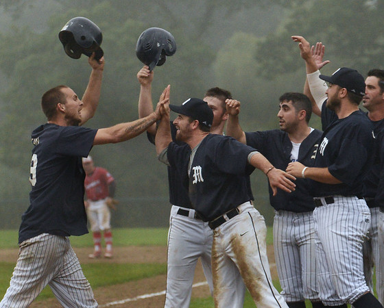 CARL RUSSO/staff photo GLOUCESTER TIMES: Manchester Mariner Mike Cain, far left, celebrates with his teammates after hitting a three-run homer to give his team a 5-1 lead late in the game The Manchester Mariners defeated the Rockport Townies in the first game of the ITL FInals. 8/13/2018